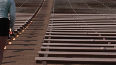 Crab-left of a woman running up the steps of a large stadium Stock Footage