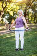 Nice retiree holding tracksticks while posing Stock Photos