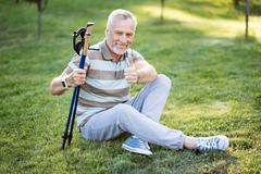 Good-looking old man sitting on grass with his legs crossed Kuvituskuvat