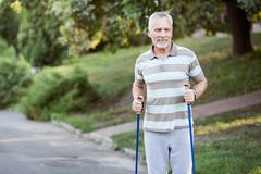 Active old man jogging in summer park Stock Photos