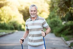 Active senior citizen jogging in the park with tracksticks Stock Photos