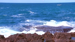Wide shot of waves breaking on the shoreline with a small fishing boat distant. Stock Footage