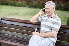 Happy nice-looking senior citizen smiling while talking on the phone Stock Photos
