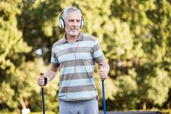 Senior citizen listening to music while walking in the park Stock Photos
