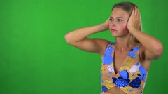 Young pretty blond woman is afraid (woman covers his ears) - green screen Stock Footage
