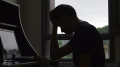 Depressed man reading bad news on laptop, male having financial problems Arkistovideo