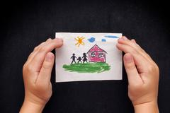 Child protects a drawn house with family Stock Photos