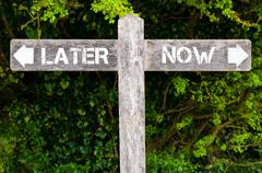 LATER versus NOW directional signs Stock Photos