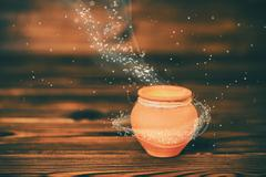 Concept greeting card of ceramic pot with mystical miracle light on wooden ba Stock Photos