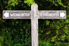 WEAKNESS versus STRENGTH directional signs Stock Photos