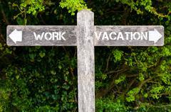 WORK versus VACATION directional signs Stock Photos