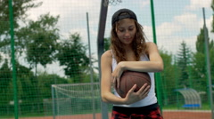 Happy girl smiling to the camera on sports field and holding basketball Stock Footage