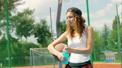 Girl holding basketball and drinking energy drink on sports field Stock Footage