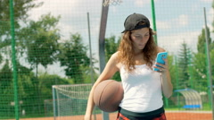 Girl holding basketball and smiling to the camera on sports field Stock Footage