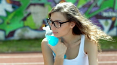 Thoughtful girl sitting on sports field and drinking energy drink Stock Footage