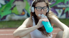 Girl listening music on headphones and drinking energy drink, steadycam shot Stock Footage