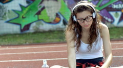 Girl listening music on headphones and moving ball, steadycam shot Stock Footage