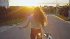 Beautiful and fashion young woman posing at the sunset with a skateboard Stock Footage