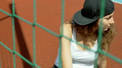 Girl sitting on sports field behind net and looking thoughtful Stock Footage