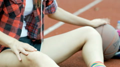Girl feeling the music while sitting on the sports field Stock Footage