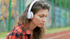 Morose girl listening music on headphones and looking thoughtful Stock Footage