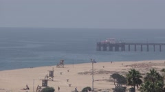 Long zoom out from Balboar Pier with Newport Pier jetty Corona Del Mar beach. Stock Footage
