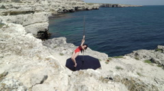 Graceful pole dancer performs poledance on a cliff above the sea Stock Footage