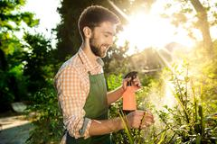 Young handsome gardener smiling, watering, taking care of plants. Flare sunlight Stock Photos