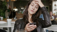 Stylish young woman uses a smartphone sitting at a table in modern cafe Stock Footage