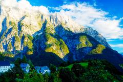 Beautiful alpine mountain landscape on summer day with little village in the Stock Photos
