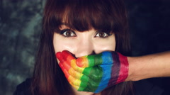 4k LGBT Shot of Rainbow Coloured Hands Man on Woman's Mouth Stock Footage
