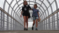 Two girls go through a transition, made of glass and steel Stock Footage