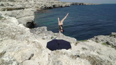 Pole dancer using portable pole fitness stage on rocky cliff by sea Stock Footage