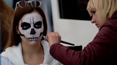 Artist applies skull make-up for guest Stock Footage
