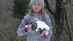 Girl playing with snow and throwing snowball Stock Footage