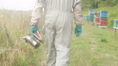 4K Bee keeper walking away from his hives holding a smoker in his hand Stock Footage