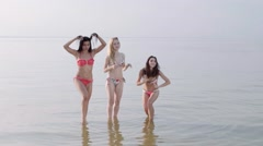 Group of Three Teenage Girls jumping In The Water At The Beach sunset. Slow Stock Footage