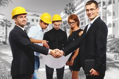 Business people shaking hands, finishing up a meeting. Construction theme Stock Photos