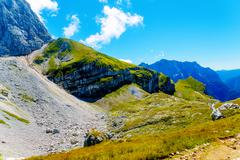 Beautiful rocky cliff in alpine mountains on summer day Stock Photos