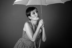 Girl vintage 50s dress with white umbrella over blue background Stock Photos