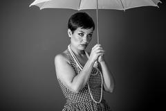 Cheerful girl vintage 50s dress with white umbrella over blue background Stock Photos