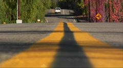 A car drives down a street in a rural area. Stock Footage