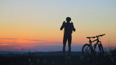 Jump on heart mountain. Silhouette happy cyclist, overcame many obstacles to Stock Footage
