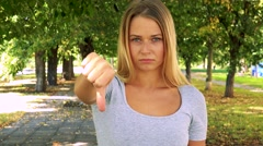 Young pretty blond woman disagrees (show thumb down) - park with trees  Stock Footage