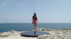 Pole dancer with portable fitness dance pole on a rock above the sea rear view Stock Footage