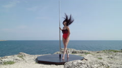 Pole dance fitness outdoor workout on the edge of rocky cliff Stock Footage