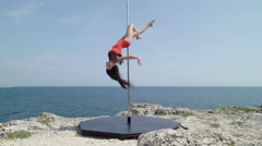 Pole dancing fitness exercise dancer performing pole tricks on the edge of rock Stock Footage