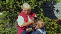 Grandmother with her little grandson petting a cat in the garden Stock Footage