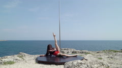 Fitness pole dance workout on the edge of rock above the sea Stock Footage