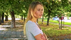 Young pretty blond woman walks and thinks about something - park with trees Stock Footage
